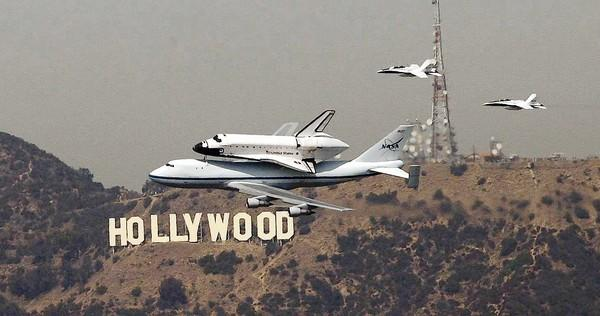 Endeavor passes the Hollywood sign (as seen from the U.S. Bank Tower in downtown Los Angeles) as the retired space shuttle makes the rounds of the Los Angeles and Orange County areas before landing at LAX on Sept. 21.