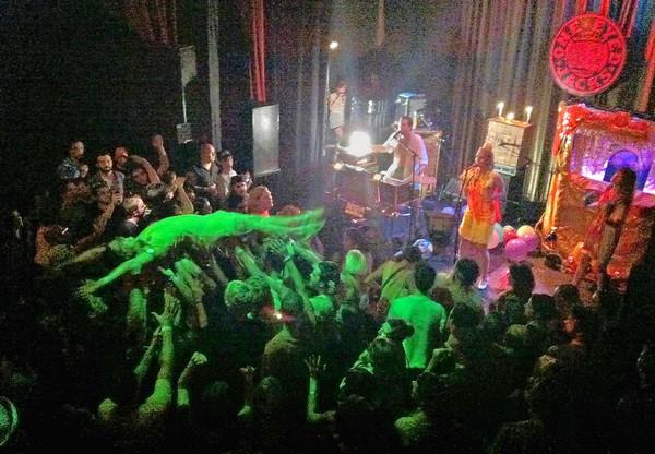 A fan crowd surfs during a riotous set by rocker Quintron at One Eyed Jacks in New Orleans.