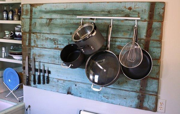 Old fence boards were installed as a backdrop for an Ikea pot rack and knife magnet.