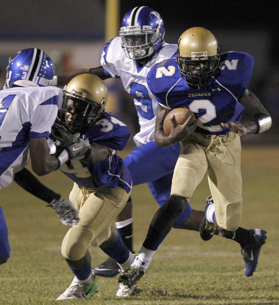 Smithfield's Bruce Cypress (right) gets by York's Tywuan Lewis to carry the ball during the first half of Friday's game.