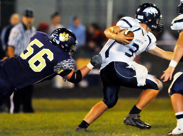 Smithsburg lineman Kyle Dinterman grabs Catoctin quarterback Peyton Laramore during Friday night's MVAL Antietam football game