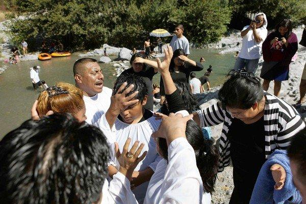 Pastor Juan Morales, left, prays after baptizing a worshiper in the East Fork of the San Gabriel River.