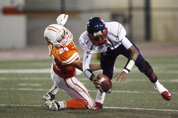 Pasadena Poly's Jake Zelek, left, tries to take the ball from Bell-Jeff's quarterback Johnathan Porter during a game at South Pasadena High School on Friday, September 28, 2012.
