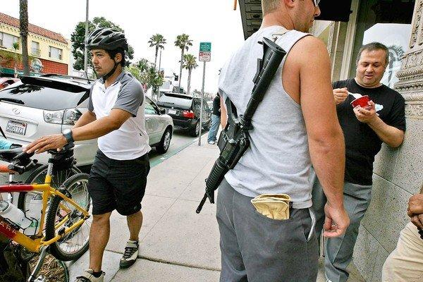 A supporter of open carry laws carries an unloaded carbine on a Hermosa Beach street, which will be illegal under a law signed by Gov. Jerry Brown.