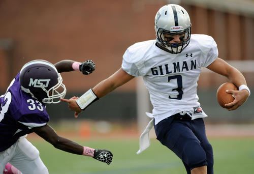 Gilman quarterback Shane Cockerille, right, pushes away Mount St. Joseph defensive back Avery Vernado.