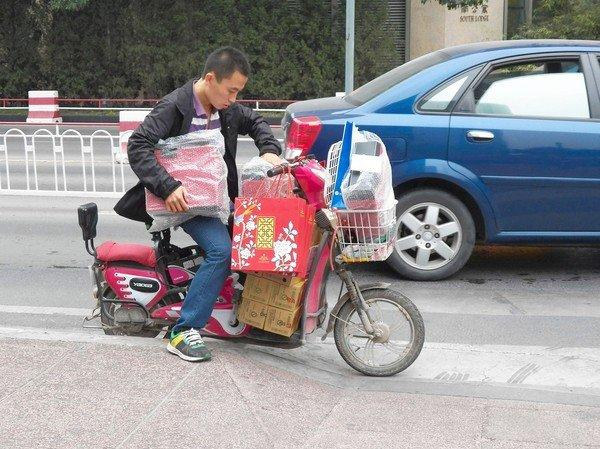A moped rider struggles to balance multiple boxes of mooncakes last week in Beijing, whose residents say mooncake deliveries add to traffic woes before the Mid-Autumn Festival.