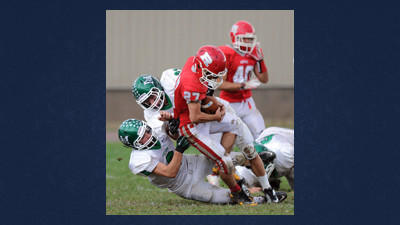 Portage Mustang defenders Evan Price, 6, and Zack Coukart, 22, team up to bring down Rockwood¿s Joel Ansell Saturday.