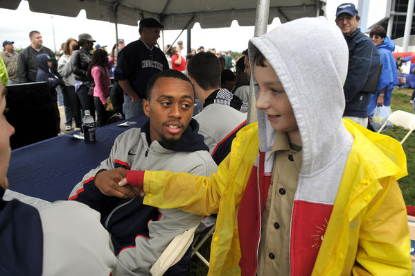 UConn guard Ryan Boatright shakes hands with James Kappelman, 12, from Boy Scout Troop 60 in Oakdale at Rentschler Field Saturday morning in East Hartford. The UConn men's basketball team was on hand to sign autographs for fans before the football team played Buffalo in a 24-17 victory.
