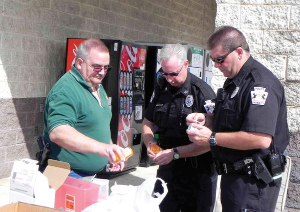 Greencastle (Pa.) Police Chief John Phillippy, Officer Ben Thomas Jr. and Officer Eric Kamoie man a table Saturday at a drug take-back event outside Food Lion in Greencastle.