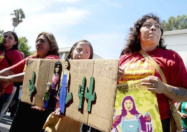 Domestic worker Sylvia Lopez, right, joins other domestic workers and their supporters at a rally at MacArthur Park in Los Angeles calling on Gov. Jerry Brown to sign into law the Trust Act. He has until Sunday night to sign or veto the bill, which would prohibit local authorities from complying with federal detention requests except when a suspect has been charged with a serious or violent crime.