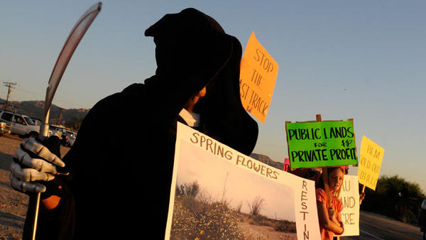 Protesters of a wind energy project just outside of Ocotillo stand alongside Interstate 8 watching 18-wheelers bring in materials to the construction site Saturday morning.