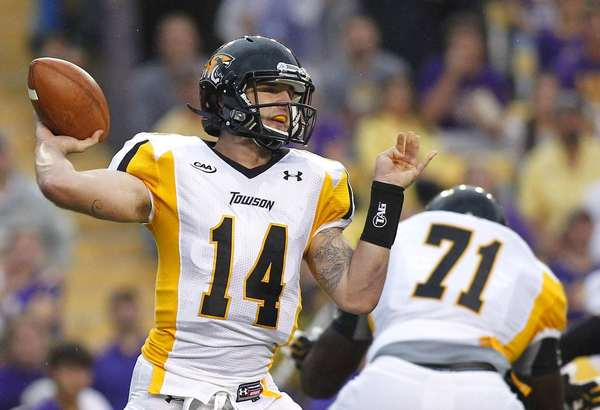 Towson quarterback Grant Enders, left, drops back to pass in the first half against LSU at Tiger Stadium.