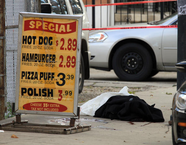 The covered body of a shooting victim is seen on the sidewalk outside of a hot dog stand on the 900 block of W. 35th St. in Chicago Sunday. Another man was wounded outside of Johnny O's hot dog stand about 5:20 a.m., authorities said.