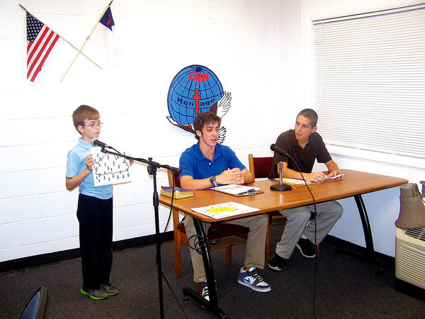 Senior Collin Poyle, seated at left, assisted by James Robinson, far left, from the fifth grade, gives the day¿s weather report while junior Abe Strickler, seated at right, prepares to make the rest of the announcements.