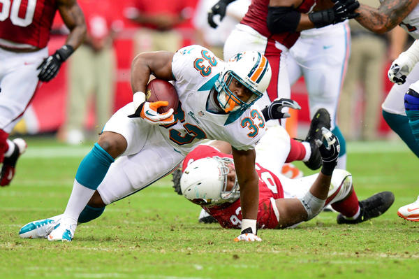 Miami Dolphins running back Daniel Thomas (33) breaks a tackle by Arizona Cardinals defensive end Calais Campbell (93) during the first half at University of Phoenix Stadium.