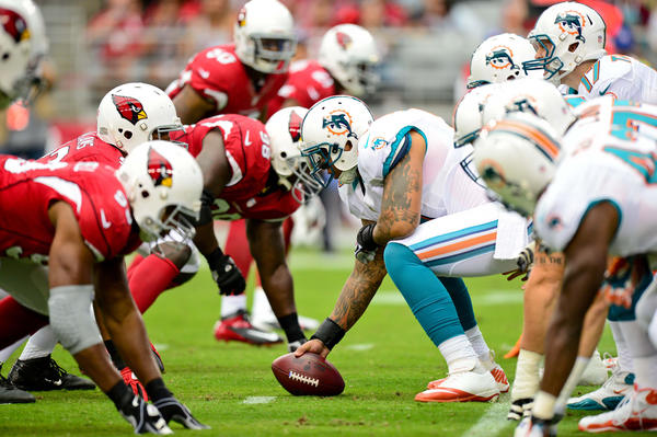 Miami Dolphins center Mike Pouncey (51) prepares to hike the ball as the Arizona Cardinals defensive line looks on during the first half at University of Phoenix Stadium.