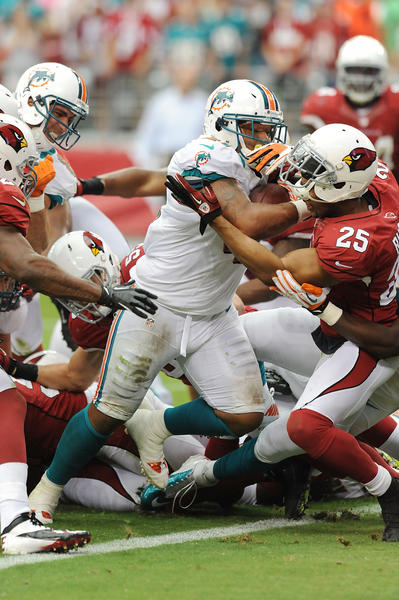 Miami Dolphins running back Daniel Thomas (33) breaks a tackle by Arizona Cardinals linebacker Jamaal Westerman (57) during the first half at University of Phoenix Stadium.