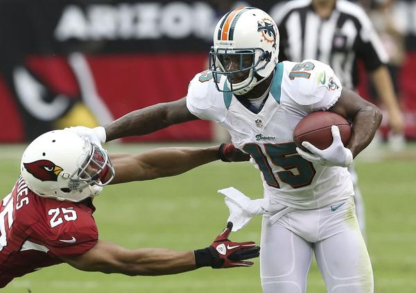 Miami Dolphins' Davone Bess (R) stiff arm's the Arizona Cardinals' Kerry Rhodes during the first half