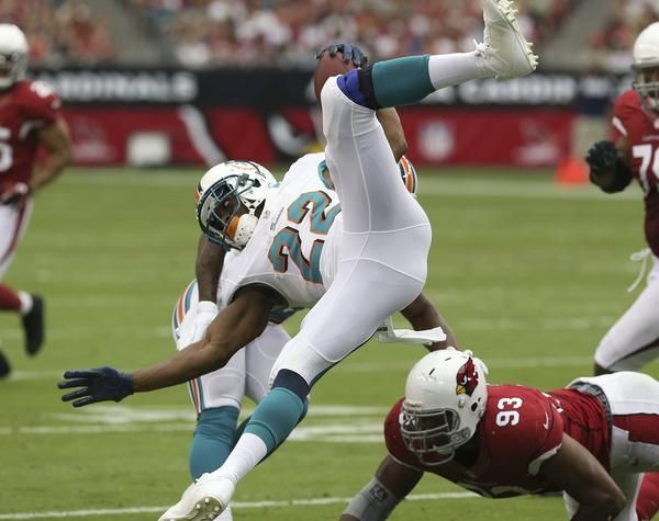 Miami Dolphins' Reggie Bush gets upended by the Arizona Cardinals' Calais Campbell (93) during the first half.
