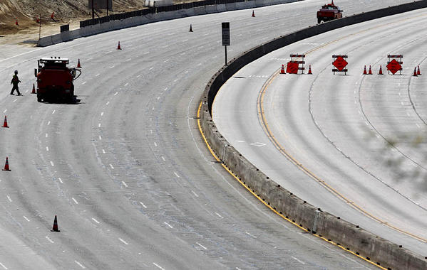 Caltrans crews work on a 405 Freeway devoid of traffic Sunday.