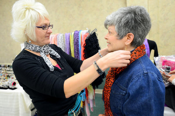"Christine ""Blondy"" Smith, left, owner of Blondy & Company, helps Joyce Debra Schiro try on a scarf during the Royal Treatment jewelry and indulgence bonanza Sunday afternoon at the Williamsport Volunteer Fire Co. The event was a fundraiser for the Hagerstown Lioness Club."