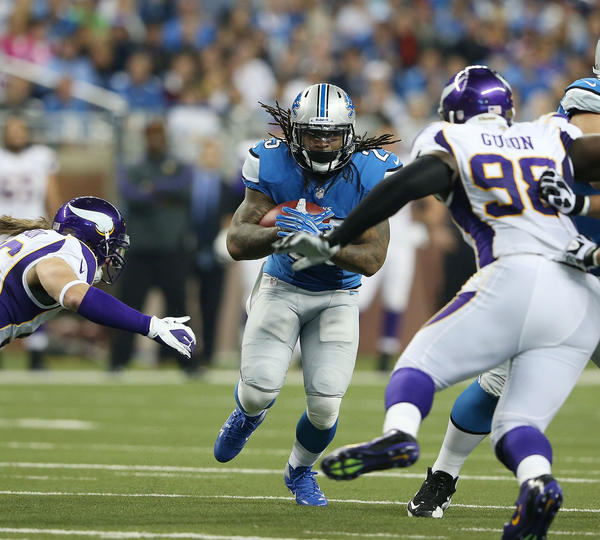 Mikel Leshoure #25 of the Detroit Lions runs for a first down as Brian Robinson #96 and Letroy Guion #98 of the Minnesota Vikings make the stop during the game at Ford Field on September 30, 2012 in Detroit, Michigan. The Vikings defeated the Lions 20-13.