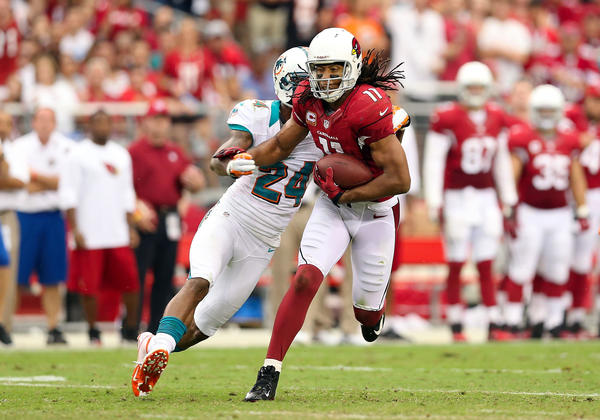 Wide receiver Larry Fitzgerald #11 of the Arizona Cardinals runs with the football after a reception against the Miami Dolphins during the NFL game at the University of Phoenix Stadium on September 30, 2012 in Glendale, Arizona. The Carindals defeated the Dolphins 24-21 in overtime.