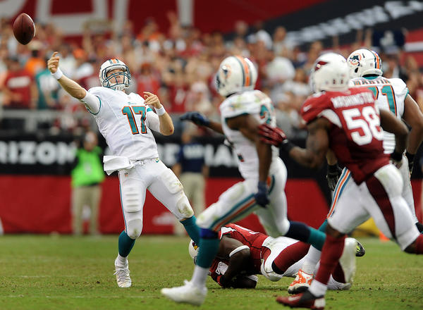 Miami Dolphin's quarterback Ryan Tannehill barely gets the ball off as he is pressured by Arizona's defense in the fourth quarter of the Dolphin's overtime loss.