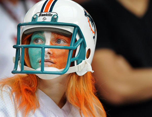 A Miami Dolphins fan sports an old-school helmet to go along with her orange painted hair as she supports her team Sunday afternoon at University of Phoenix Stadium.