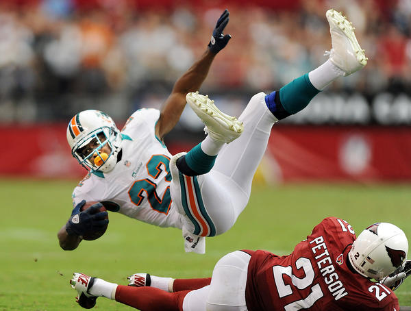 Miami Dolphin's running back Reggie Bush is upended by Arizona cornerback Patrick Peterson in the second quarter.