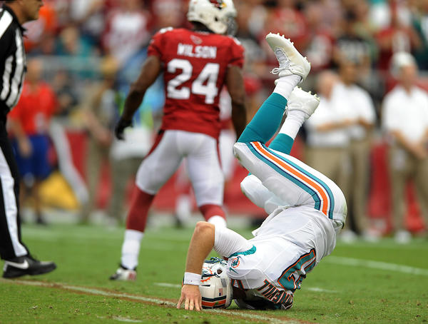 Miami Dolphin quarterback Ryan Tannehill gets upside down after taking a big hit while throwing in the second quarter.