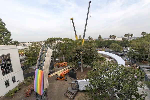 "Construction cranes are used to assemble ""Rainbow,"" a huge art piece installed by Sony Pictures Entertainment in Culver City."