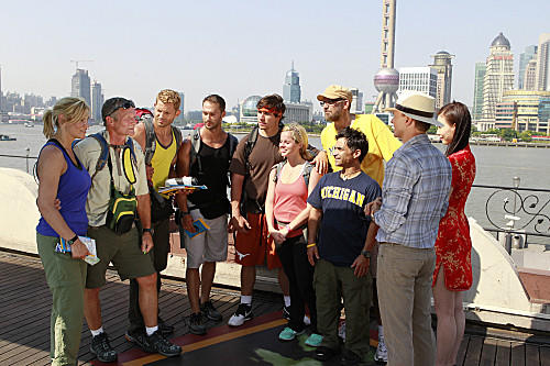 "Emmy nominated host Phil Keoghan (second from right) greets teams at the Pit Stop in Shanghai, China on ""The Amazing Race."""