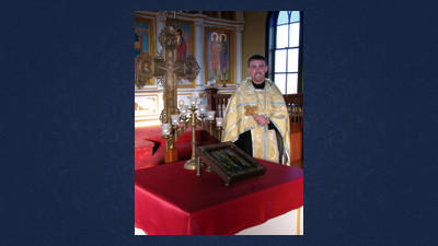 The Rev. Elijah Bremer stands among the ornate surroundings of the interior of SS Peter and Paul Orthodox Church in Boswell.
