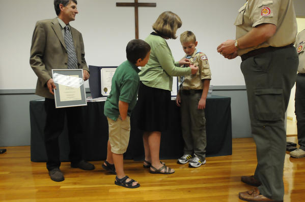 Campfield Heinrich, 12, of Boy Scout Troop 27,  looks as his mother, Anne, pins the heroism medal on him which he received from Boy Scouts of America district leaders at St. Mary's Episcopal Church in Manchester Thursday night.