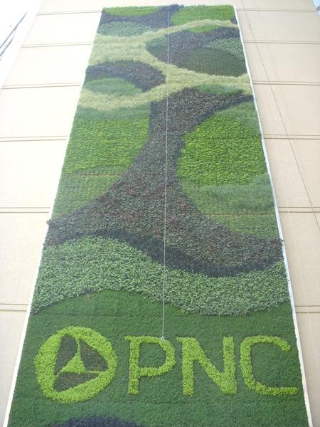 Plants growing in more than 500 recycled aluminum planters paint a green banner on PNC's Maryland headquarters building at One E. Pratt St.