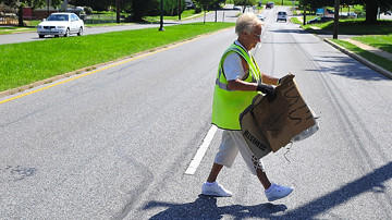 Doris Ellis crosses Wilson Boulevard with a load of trash from the median. She spends hours each day walking and picking up trash near her Brinker Drive home.