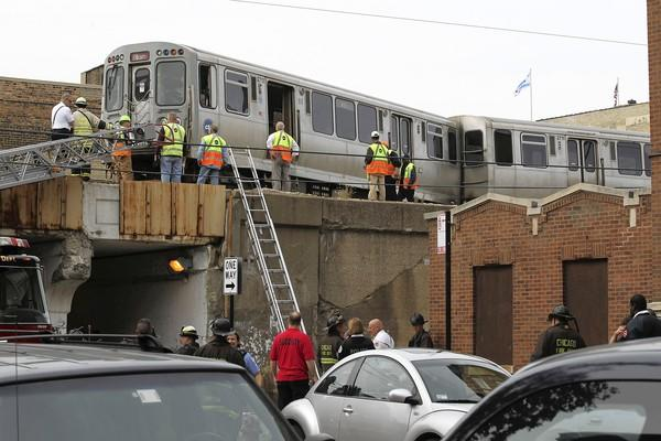 Officials surround a Red Line train after a switching mishap Monday at Rosemont Avenue. No one was injured. Passengers were taken to the Loyola stop and exited there.