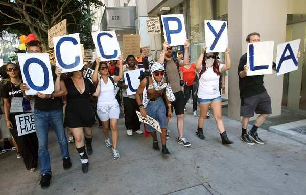 Protesters march along 7th Street in downtown Los Angeles on the one-year anniversary of the Occupy Los Angeles movement.