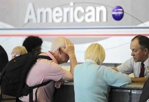 American Airlines fliers get help Monday at O'Hare International Airport. Mechanics and reservations agents are working overtime to handle problems caused by delays.