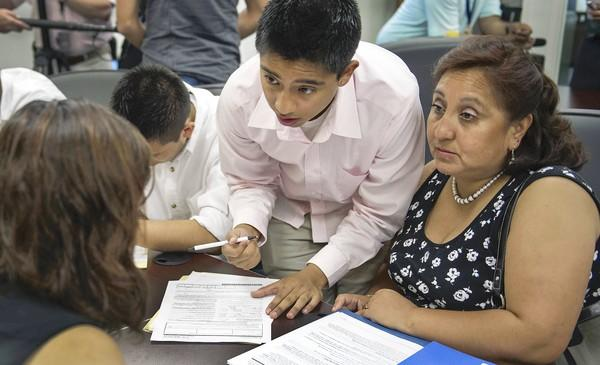 Applicants and relatives fill out paperwork in Washington for the Obama administration's work permit program. All applicants must prove they came to the U.S. before age 16 and have been here continuously for the last five years, among other requirements.