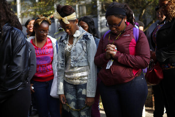 Aviance Sanson, left, and Dorothy Finley, center, join students in prayer outside Walter H. Dyett High School after the group filed a complaint under Title VI of the Civil Rights Act of 1964 against the school's phaseout.