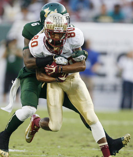 FSU wide receiver Rashad Greene runs with a pass as he's tackled by USF defensive back Kayvon Webster during the FSU at USF college football game at Raymond James Stadium in Tampa on Saturday, September 29, 2012.