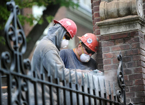(Right) Darwin Bruce and (Left) his son, Coby Bruce, both employees of Caretti Inc. out of Camp Hill, PA, remove mortar from between the bricks of pillars at Lafayette College on Tuesday.