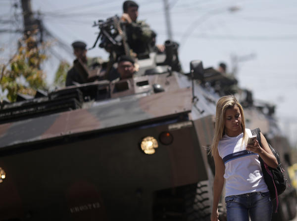 "A student walks past a Brazilian Army tank during a patrol of the Muquico slum in Rio de Janeiro. Brazilian soldiers and marines started a patrol in Rio de Janeiro slums to guarantee ""democratic freedom"" and allow candidates to campaign for the upcoming October 7 elections for the mayor and city council."