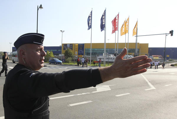 A police officer gestures outside an Ikea store during a bomb alert in Anderlecht, a suburb of Brussels. About 1,500 shoppers were evacuated on Saturday because of a suspect parcel, police said. No bomb was found.