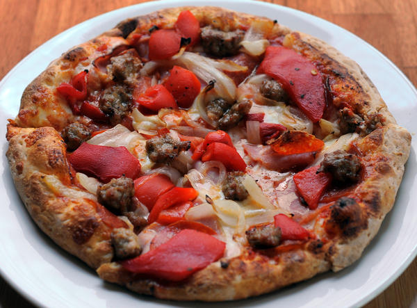 Toss special pizza ($12.00), made with Italian sausage, caramelized onions, roasted red peppers, pepperoni, ham, and mozzarella and provolone cheeses in a homemade tomato sauce, at Toss in Govans.
