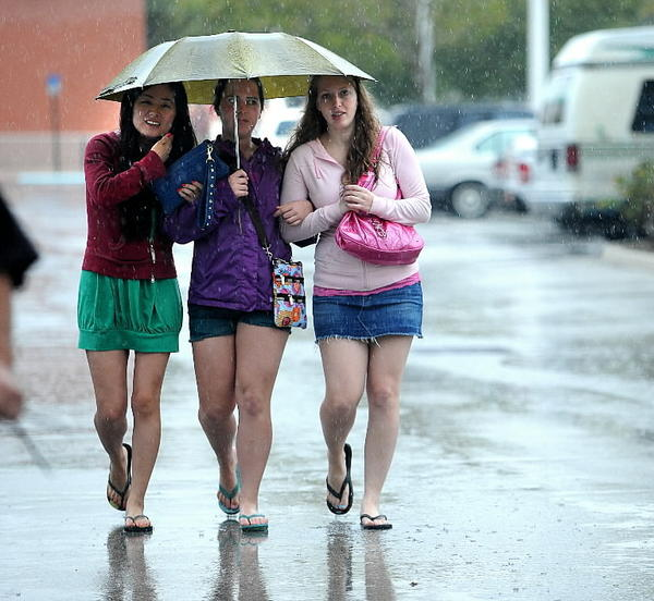 Three young women share an umbrella in Fort Lauderdale.