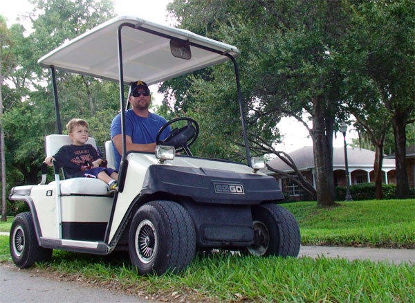Dan Yates, 37, of Windermere, picks up his son Finnigann, 4, from school at First Baptist Church Windermere. Last month, the town of Windermere became latest community in Central Florida to pass a golf cart ordinance.