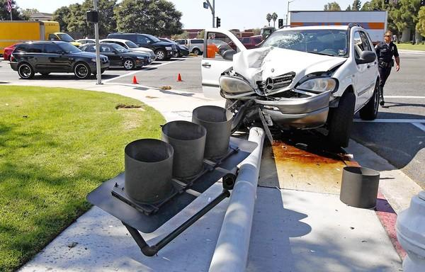 A Mercedes SUV knocked down a traffic signal at the corner of Sunflower Avenue and Harbor Boulevard in Costa Mesa, snarling traffic Tuesday. The driver was uninjured.